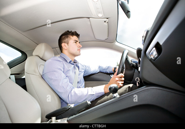 a young man driving the car - Stock Image