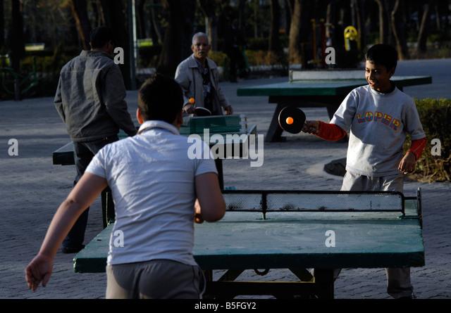 Iranians play table tennis at Park e Shahr, central Tehran at dusk - Stock Image