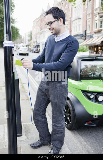 Man charging electric car on street - Stock Image