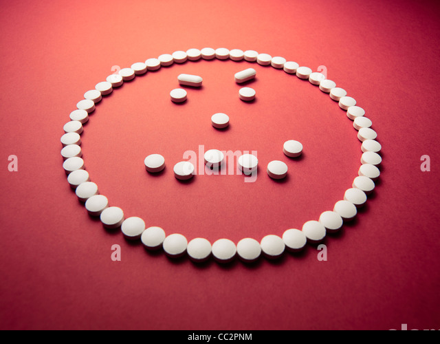 angry face made out of pills and drugs - Stock Image