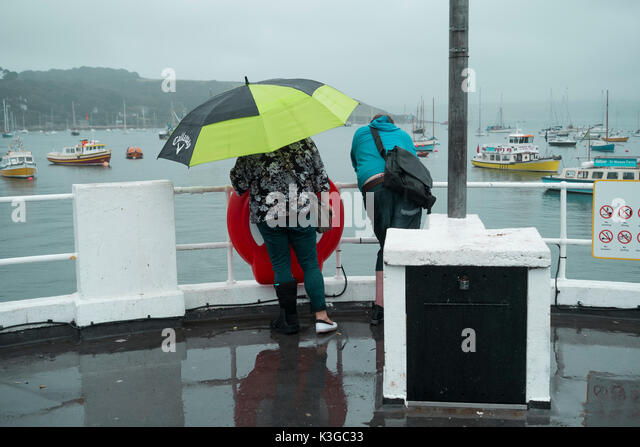 Falmouth, UK. 03rd Sep, 2017. A couple enjoy a wet walk along the Prince of Wales Pier, Falmouth Cornwall under - Stock Image