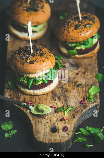Healthy vegan burgers with beetroot and quinoa patty, arugula, avocado sauce, wholegrain bun on rustic wooden board - Stock Image