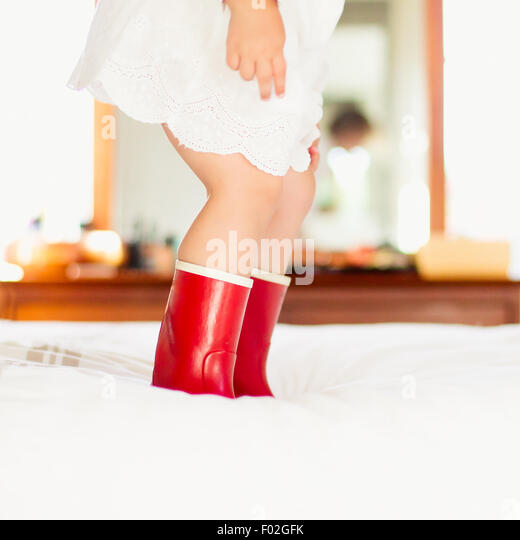 Close-up of a girl in red boots jumping on a bed - Stock Image