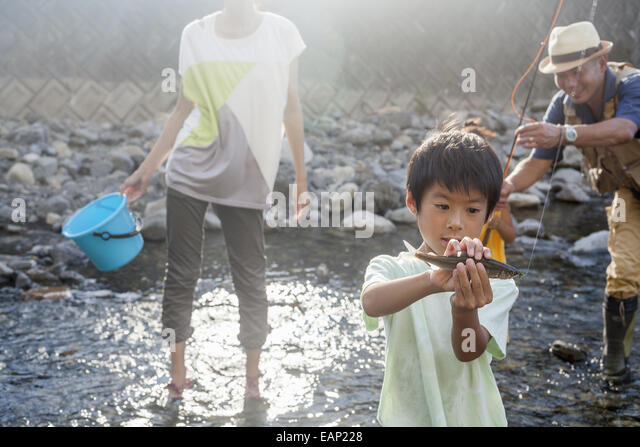 Family fishing in a stream. - Stock Image