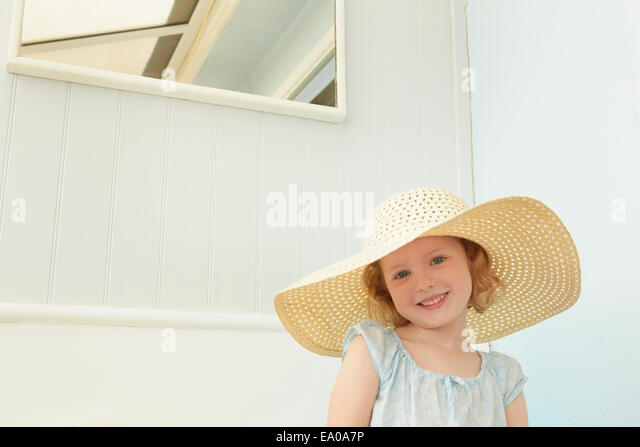 Portrait of girl with sunhat on in holiday apartment - Stock Image