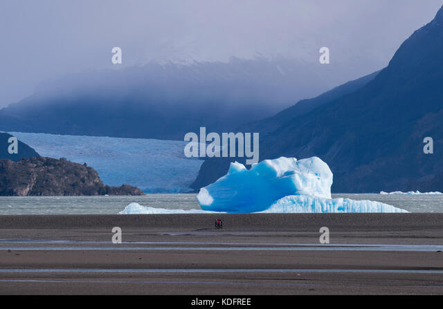 Tourists walking on the bech at Lago Grey, in Torres del Paine, Chile - Stock Image