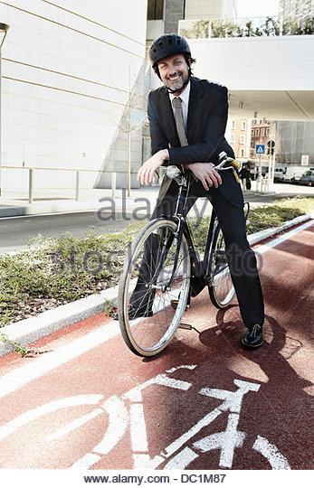 Mid adult businessman on bike on cycle path, portrait - Stock Image
