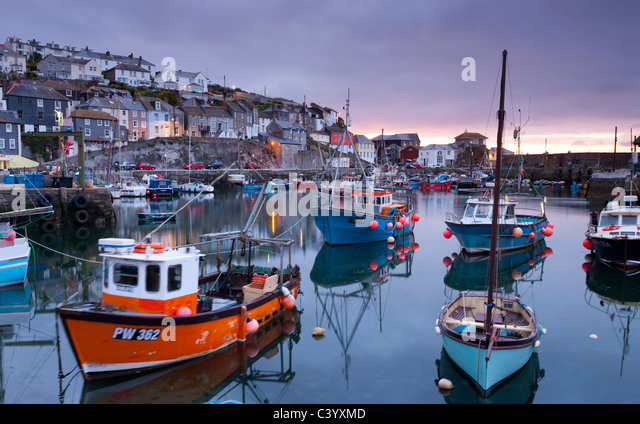 Fishing boats crowd a placid Mevagissey Harbour at dawn, Mevagissey, South Cornwall, England. Spring (May) 2011. - Stock Image