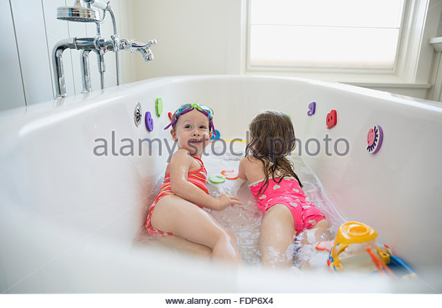 Sisters playing in bath - Stock Image