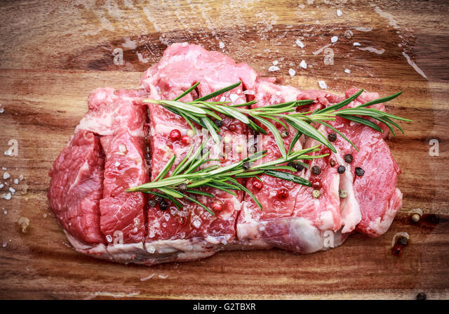 Raw beef steack with peppercorn and rosemary - Stock Image