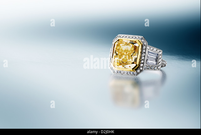 Yellow Canary Diamond Ring on blue silver background - Stock Image