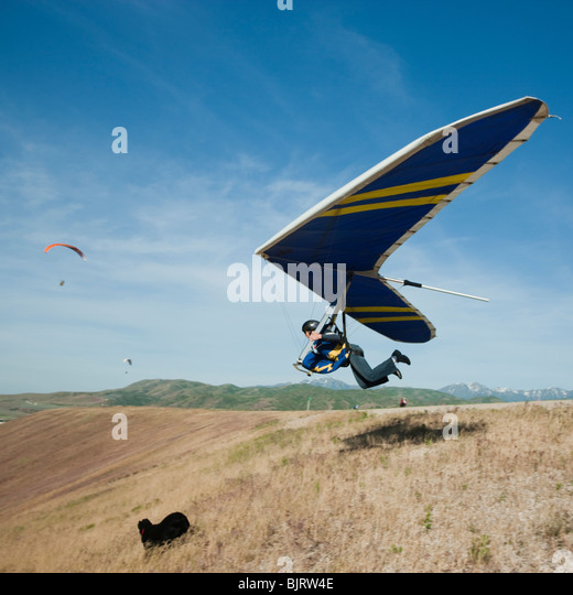 USA, Utah, Lehi, young man taking off with hang glider - Stock Image