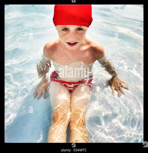 Boy with a red swimming cap on in a shallow pool looking directly at the camera. - Stock Image