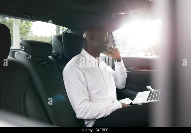 African businessman with laptop talking on mobile phone inside a car. Young entrepreneur working during travelling - Stock-Bilder