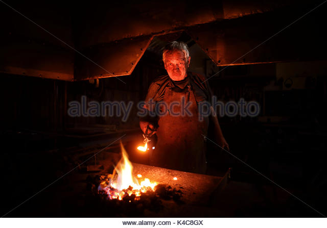 Authentic Old-Fashioned Blacksmith heating metal in red hot burning coals at his forge - Stock Image