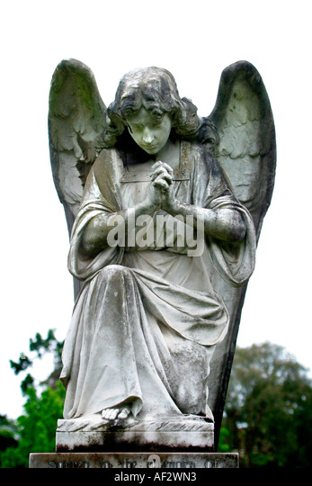 Praying angel in church graveyard - Stock Image