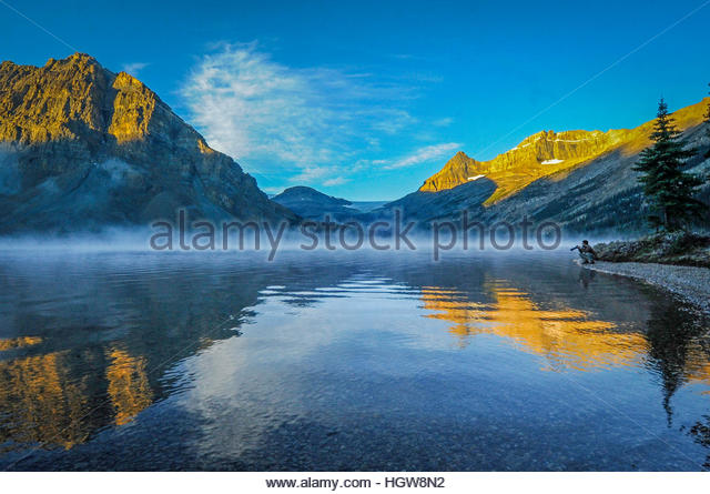 A photographer admires reflections of Crowfoot Mountain and Mount Thompson in Bow Lake. - Stock-Bilder