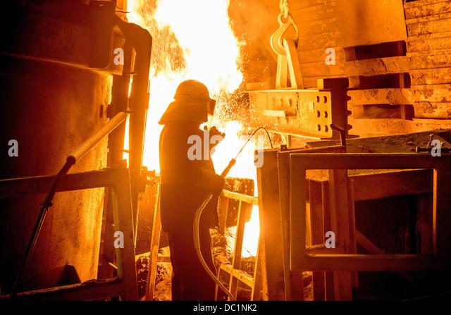 Steel worker in front of furnace fire in steel foundry - Stock Image