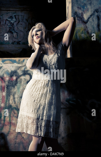 Woman covered in dust against graffiti covered wall - Stock Image