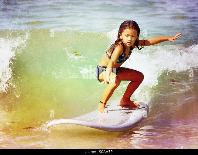 Little girl surfing. - Stock Image