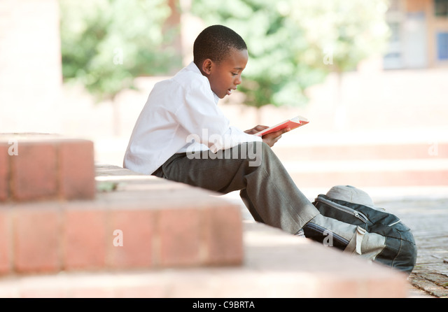 Boy reading on steps outside school, Johannesburg, Gauteng Province, South Africa - Stock Image