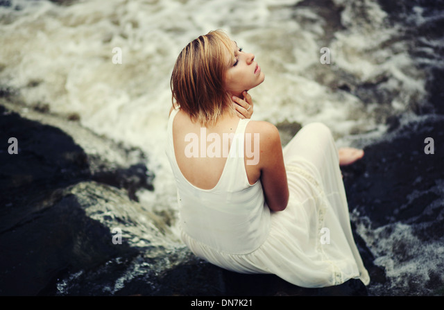 Young woman in white dress sitting on a creek - Stock Image
