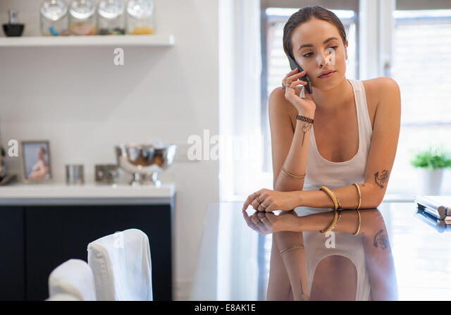 Sad looking young woman leaning on kitchen table chatting on smartphone - Stock Image