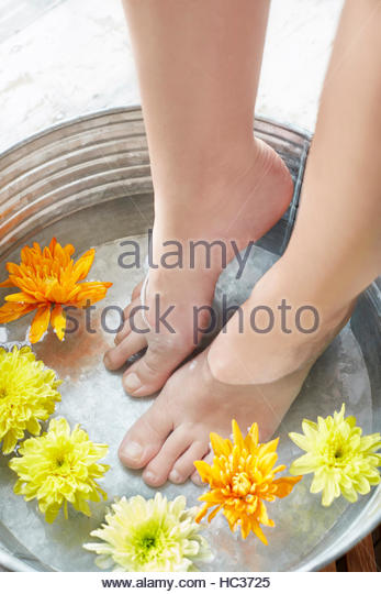 Woman bathing feet in water with flowers. - Stock Image