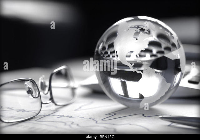 Toned image of glass globe with stock charts, calculator and spectacles - Stock Image