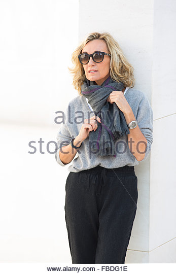 Mature Woman Leaning against Wall adjusting Scarf - Stock Image