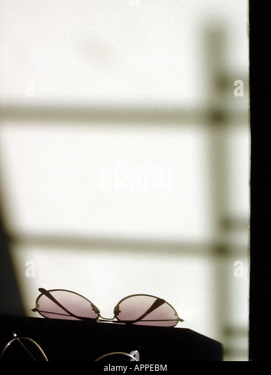 Artistic Photographic of a Shadow Cast on a Wall by a Pair of Aviator Style Sunglasses Copy Space - Stock Image