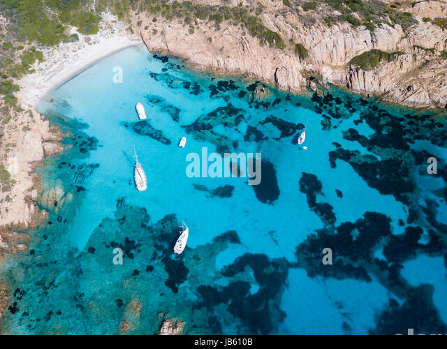 Aerial view of boats in front of Mortorio island in Sardinia. Amazing beach with a turquoise and transparent sea. - Stock Image