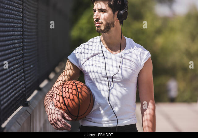 Young male basketball player walking over footbridge listening to headphones - Stock Image