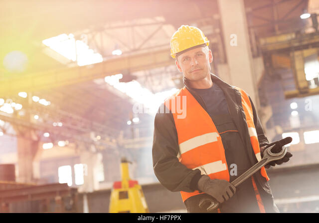 Portrait confident steel worker holding large wrench in factory - Stock Image