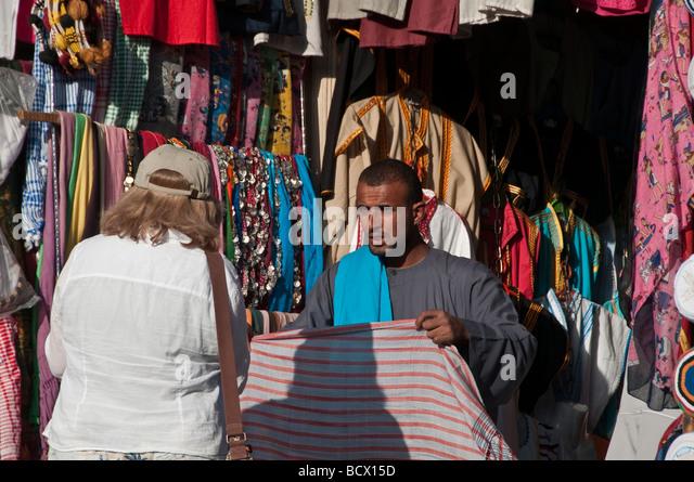 Egypt Kom Ombo woman tourist bargains with Egyptian souvenir seller - Stock Image