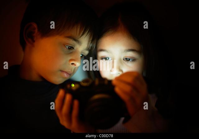 Boy and girl look at digital camera screen - Stock Image