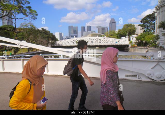 Singapore Singapore River Boat Quay Cavenagh Bridge Asian man woman Muslim hijab - Stock Image