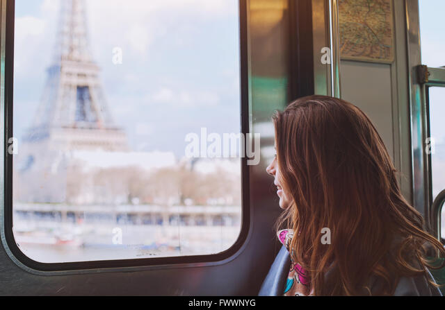 tourist looking to the Eiffel Tower through the window of metro in Paris, smiling girl visiting France - Stock Image