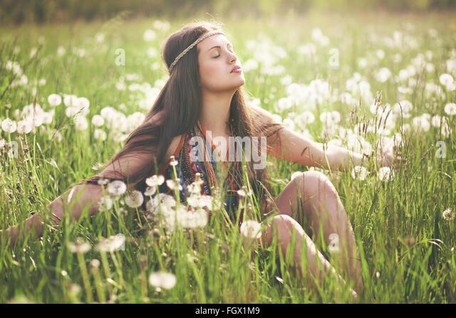Beautiful hippie woman enjoying sun light in flowered meadow. Harmony with nature - Stock Image