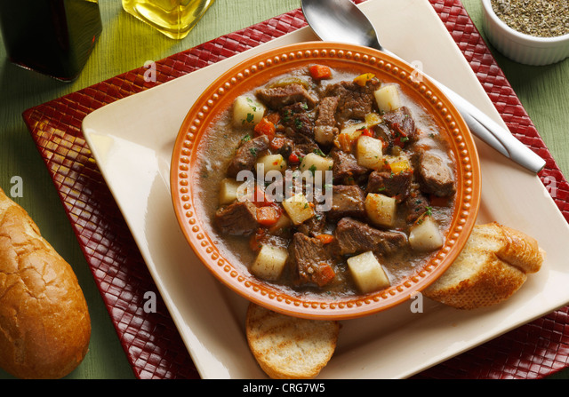 Close up of plate of stew and bread - Stock Image