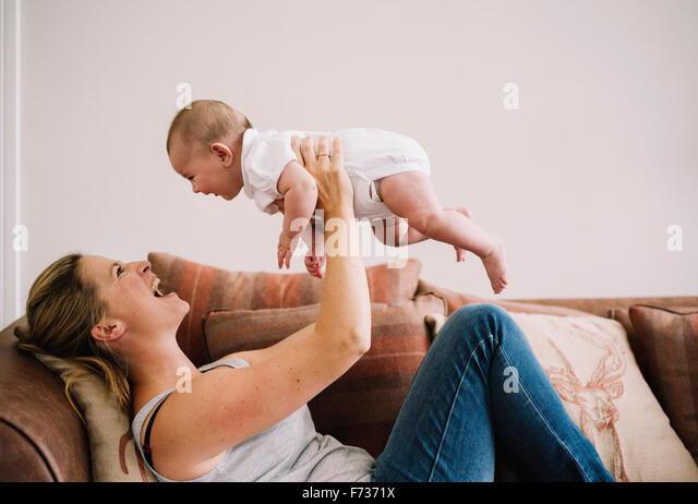 A woman lying on a sofa playing with a baby girl. - Stock Image