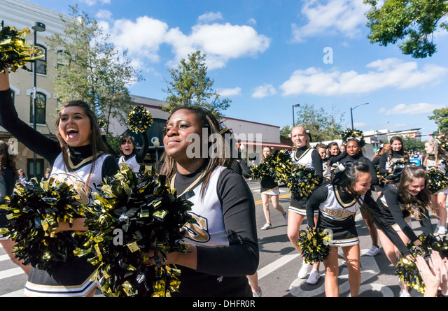 Buchholz High School cheer leaders in yellow and black costumes with gold pom poms, UF 2013 Homecoming Parade. USA - Stock Image