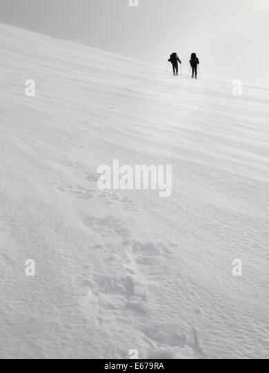 two men with heavy backpacks crossing a snowfield on snowshoes in  winter mountains with tracks in forground - Stock Image