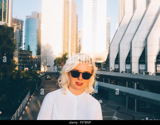 Portrait Of Woman Against Skyscrapers - Stock Image