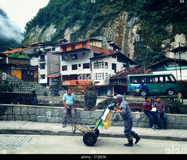 Everyday life goes by on the streets of Aguas Calientes, the jumping off point for Machu Picchu, Peru - Stock-Bilder
