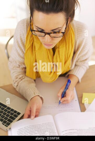 College student too busy with her book research - Stock Image