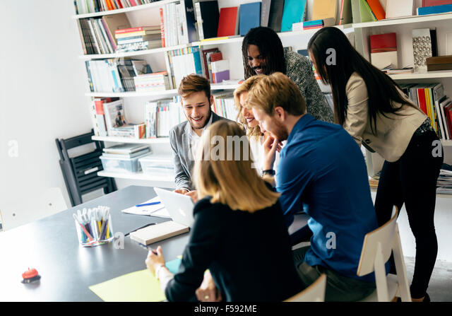 Brainstorming by a group of people in a nice office - Stock Image