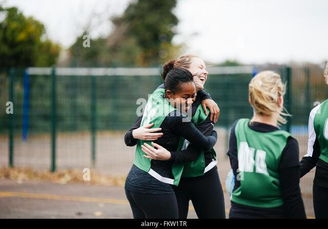 Happy female netball team celebrating win on netball court - Stock Image