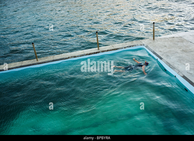 A swimmer floating and snorkeling in a seaside pool. - Stock-Bilder
