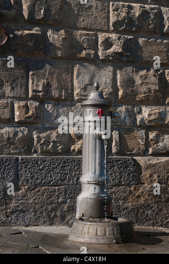 Water flows from a public water tap in a piazza in Florence, Italy. - Stock Image